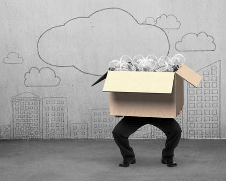 Businessman holding cardboard box with light bulbs inside, on clouds and city buildings doodles of concrete wall background.