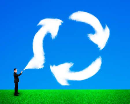 Homme d'affaires pulvérisant des nuages en forme de symbole de recyclage dans le ciel bleu et fond d'herbe verte.
