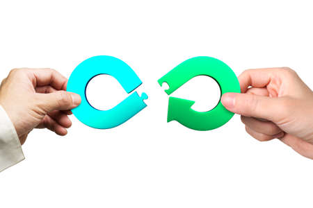Circular economy concept. Male and female hands assembling arrow infinity recycling symbol of jigsaw puzzle pieces, isolated on white background.