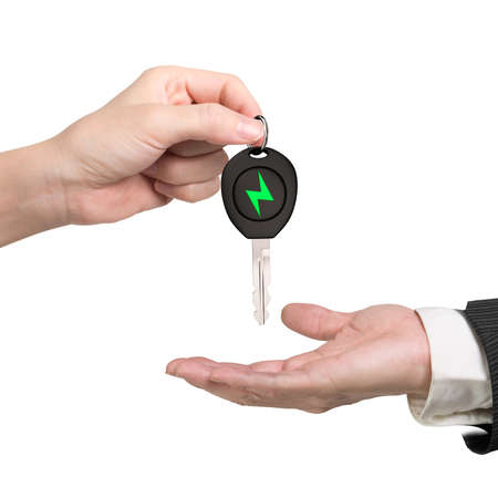 Green energy electric car and Eco-friendly environmental protection concept. Woman hand giving electric car key with green lightning bolt sign to man hand, isolated on white background.