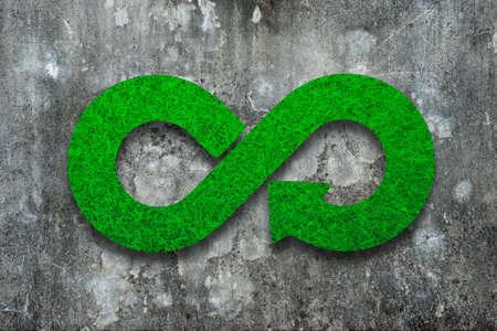 Grünes umweltfreundliches und Kreislaufwirtschaftskonzept. Infinity-Pfeil-Recycling-Symbol mit grüner Grasbeschaffenheit auf schmutzigem Betonwandhintergrund.