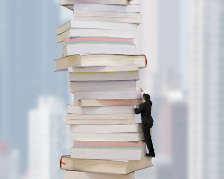 Reading and learning a mountain of new knowledge concept. Businessman climbing high stack of books with city buildings skyscraper background. Banque d'images