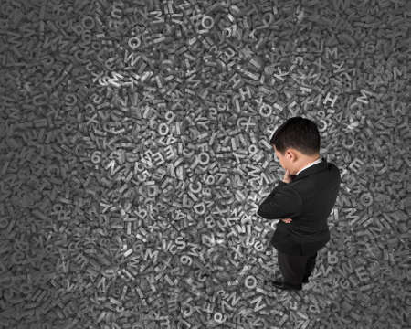 Big data concept, Thinking business man standing and looking at huge amount of 3d dark grey concrete letters and numbers texture background.