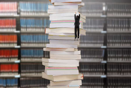 Climbing businessman hang on high stack of books with blur bookshelfs background. Reading and learning a mountain of new knowledge concept.