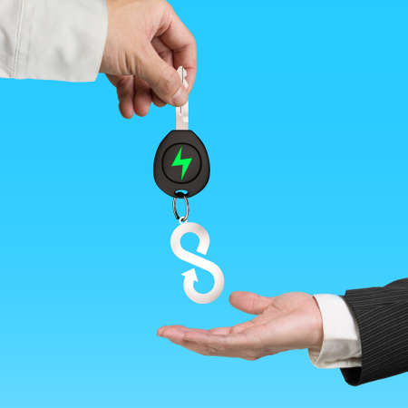 Green energy electric car, lightweight high strength speed and circular economy concept. One hand giving electric car key with sheet metal keyring of infinity arrow symbol to another, isolated on blue background.