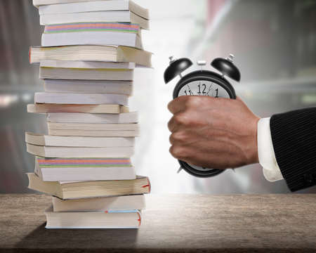Concept of many books need to read, but not enough time. Man fist clenched the deformed alarm clock in anger with stack of books on wooden desk and bookshelf background.
