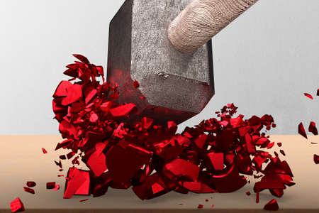 Sledgehammer smashing red percentage sign cracked on wooden table with concrete wall background.