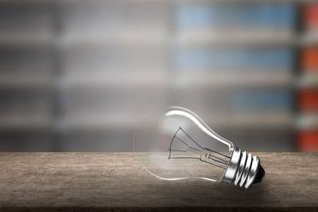 One light bulb on wooden desk, isolated on bookcases blur background.