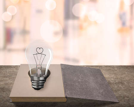 Opened old book with heart wire shape of light bulb on wooden table, isolated on blur background.