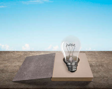 Opened old book with hope word wire shape of light bulb on wooden table, isolated on blue sky background.