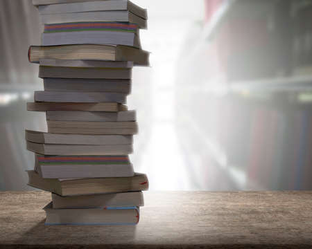 Stacking books on wooden desk with blur bookshelfs background in the library room. Education and knowledge high as a mountain concept.