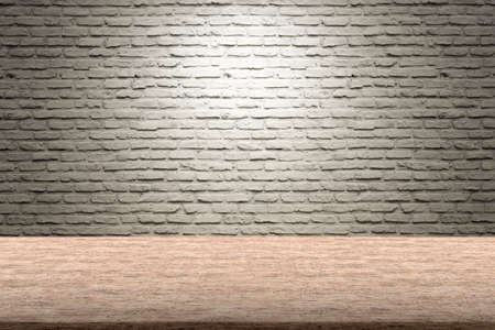 Old brown wooden table with white bricks wall background, bright white light, copy space.