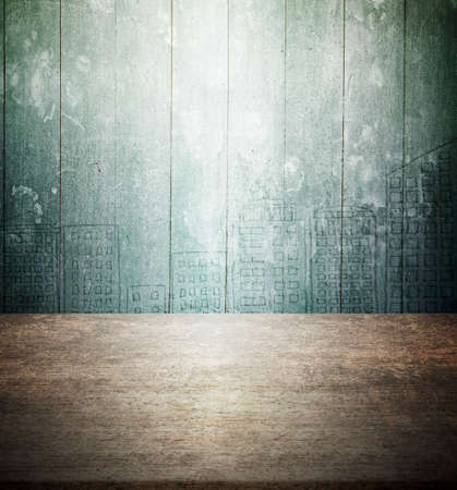 Old brown wooden table with green mottled wood wall background of city buildings doodles, copy space. Banco de Imagens