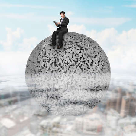 Big data concept. Businessman using digital tablet and sitting on gray concrete ball of huge amount 3d letters and numbers, on cloudy sky cityscape background. Banco de Imagens