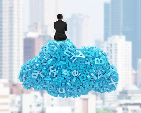 Big data and cloud computing concept. Rear view of businessman sitting on cloud of blue letters and numbers, on city buildings cityscape background. Banco de Imagens