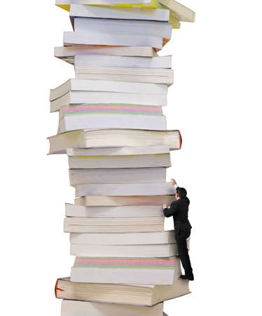 Reading and learning a mountain of new knowledge concept. Businessman climbing on high stack of books, isolated on white background. Banco de Imagens