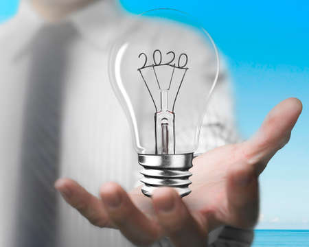 Businessman hand holding light bulb with 2020 wire shape, front view, blue sky sea background. Banco de Imagens