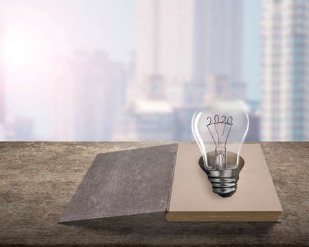 Opened old book with 2020 wire shape of light bulb on wooden table, isolated on bookcase blur background.