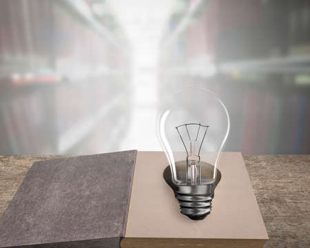 Opened old book with light bulb on wooden table, isolated on bookcases blur background.