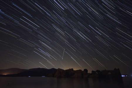 Una vista de una lluvia de meteoritos y la Vía Láctea con árboles recortados en primer plano. Paisaje de verano de naturaleza de cielo nocturno. Observación de la lluvia de meteoritos de las Perseidas.