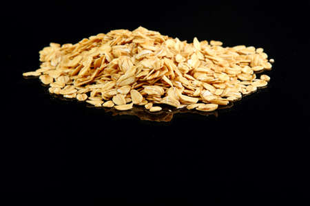 Macro image of rolled oats on a black background