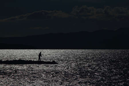 Fishing on the lake at sunset. Silhouette of a fisherman