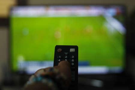 A person with a TV remote controls. Reklamní fotografie