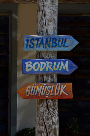 signboards with arrows on a wooden pole. Istanbul, Bodrum, Gumusluk
