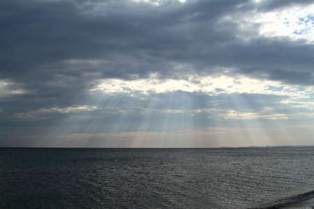 Sun rays beaming through picturesque clouds above the sea. Sun, clouds and water, sea photography.