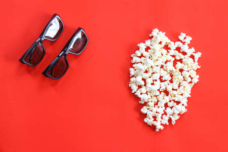 Popcorn for watching a movie in a Cup with 3D glasses on a red background. Archivio Fotografico