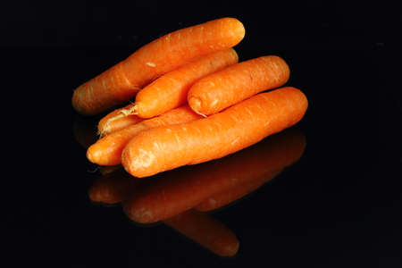 Young carrots isolated on black