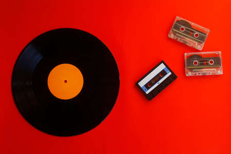 Audio cassette, vinyl record on a red background. Retro style. Top view