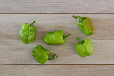 Organic green pepper in wooden plate on dark wooden table background, top view, copy space 写真素材