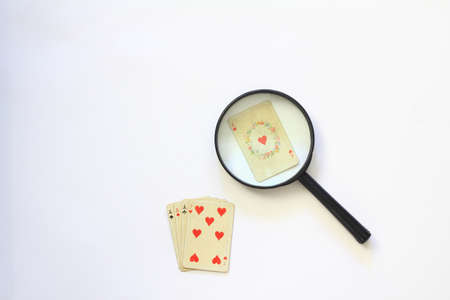 playing cards isolated on white background. magnifying and deck of poker cards on table as symbol for gambling.
