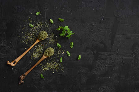 mint on wooden spoon isolated on black background. herbs and spices on a wooden background 写真素材