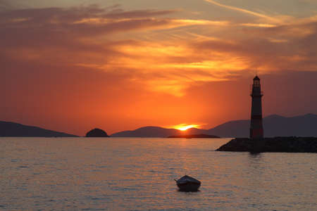 Seascape at sunset. Lighthouse on the coast. Seaside town of Turgutreis and spectacular sunsets