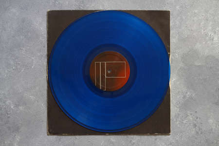 Aged black paper cover and blue vinyl LP record isolated on stone background