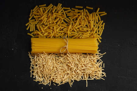Italian pasta panorama, a flat lay of various sorts of pasta, top shot on a black background Foto de archivo - 160972549