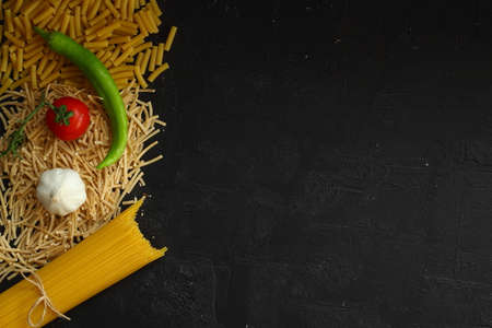 Italian pasta panorama, a flat lay of various sorts of pasta, top shot on a black background