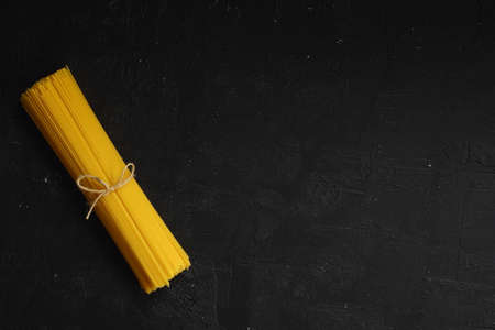 Flat lay of spaghetti for cooking italian pasta over black background. Top view of traditional italian cusine concept Foto de archivo