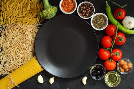 Italian Food background on black stone table. Top view. Foto de archivo