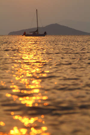 Alone sailboat at sunset. Atmospheric seascape with orange sun. Foto de archivo - 161212880
