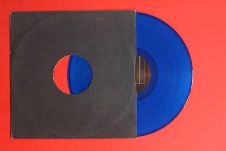 Aged black paper cover and blue vinyl LP record isolated on Red background