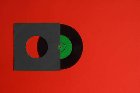 Aged paper cover and vinyl LP record isolated on Red background. 45rpm Vinyl Record with Sleeve. Foto de archivo