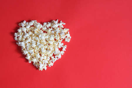 Love cinema concept of popcorn. Heart shaped white fluffy popcorn on red background with empty space for text. Valentine days concept.