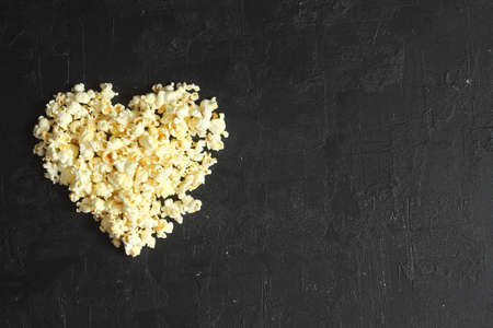 Love cinema concept of popcorn. Heart shaped white fluffy popcorn on black background with empty space for text. Valentine days concept.