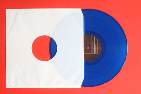 Aged White paper cover and blue vinyl LP record isolated on Red background Foto de archivo