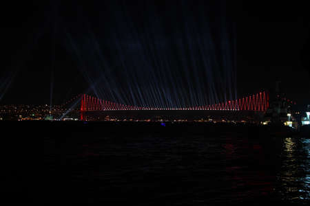 Fireworks over Istanbul Bosphorus during Turkish Republic Day celebrations. Bosphorus Bridge with red lighting and lasers at night time.