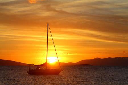 Alone sailboat at sunset. Atmospheric seascape with orange sun.
