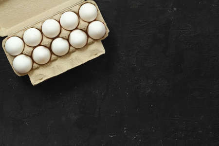 Raw White Eggs in a paper box on a black background, top view. Copy Space for text.